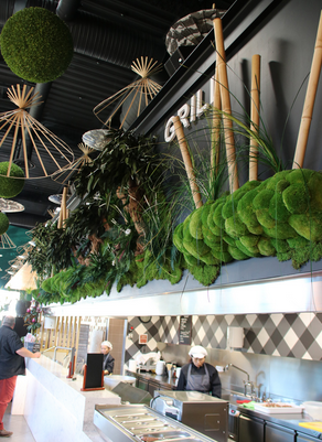緑の壁のそばに植えられたボリューム盆栽と竹のレストランサーラム装飾