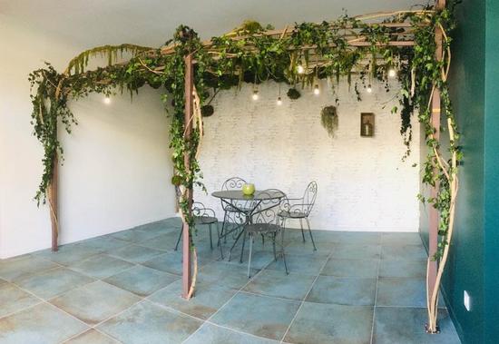 Oliv'pizzaで安定化した植物の植えられたパーゴラ